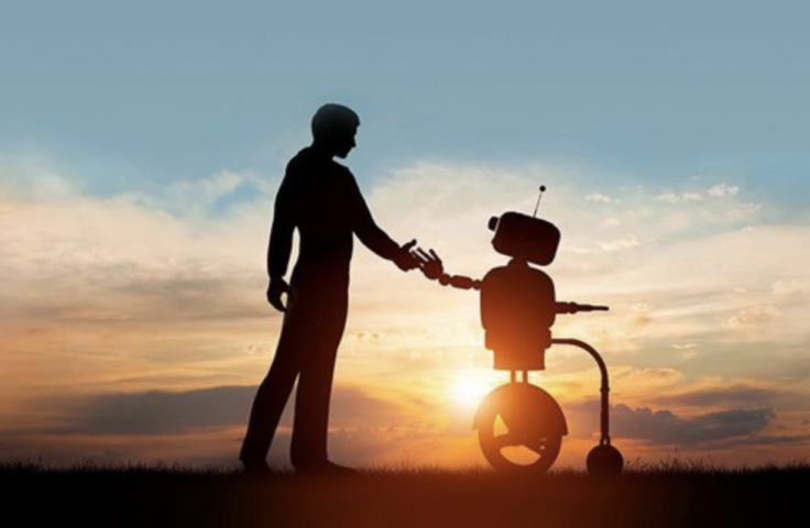 Man holding robot with wheels at sunrise